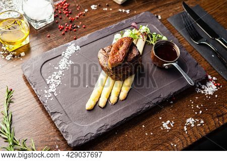 Tournedos Rossini. Foie gras, Black Angus beef tenderloin, white asparagus, red wine sauce. Delicious healthy traditional food closeup served for lunch in modern gourmet cuisine restaurant