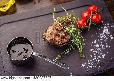 Lamb steak with cherry tomatoes and wine sauce. Delicious healthy traditional food closeup served for lunch in modern gourmet cuisine restaurant