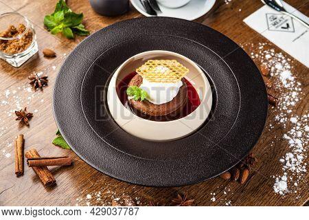 Chocolate fondant. Dark chocolate, raspberry sauce, vanilla ice cream dessert. Delicious healthy traditional food closeup served for lunch in modern gourmet cuisine restaurant