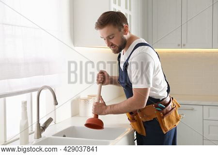 Plumber Using Plunger To Unclog Sink Drain In Kitchen