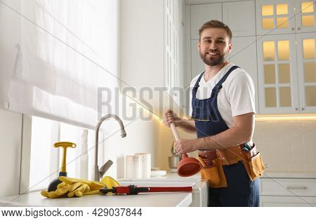 Plumber With Plunger Near Clogged Sink In Kitchen