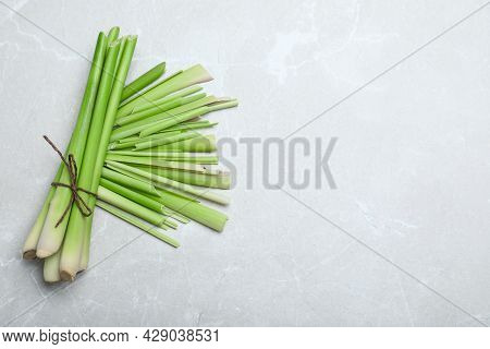 Bunch Of Fresh Lemongrass On Light Table, Flat Lay. Space For Text