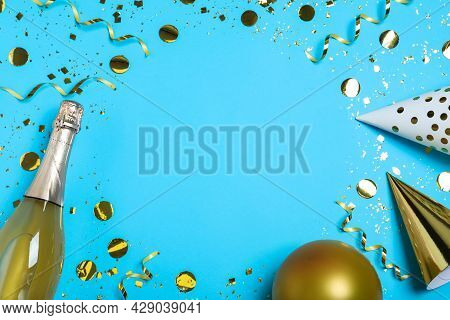 Frame Of Birthday Decor And Sparkling Wine On Light Blue Background, Flat Lay. Space For Text