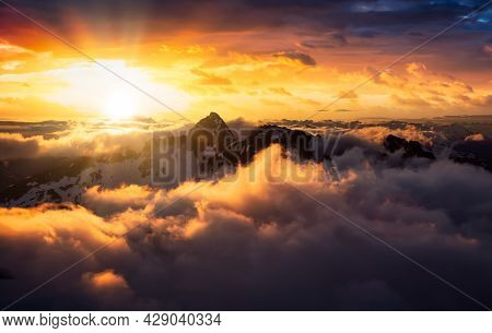 Aerial View From Airplane Of Snow Covered Canadian Landscape In Winter. Colorful Orange Sunset Sky A