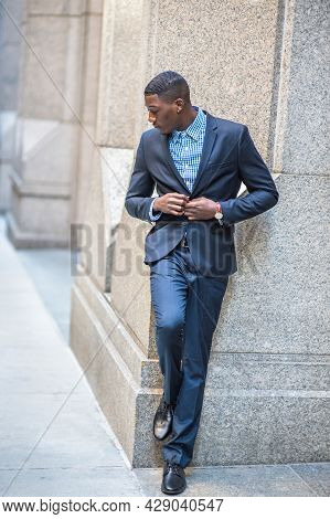Lowing His Head, A Young Black Businessman Is Standing Outside And Into Deeply Thinking