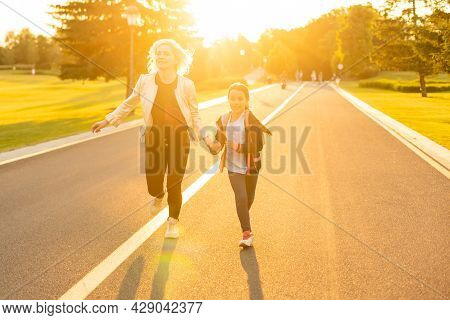 Mother And Little Daughter Go To School. Woman Looks At Her Watch, Hurries, Is Late, Quickly Goes.