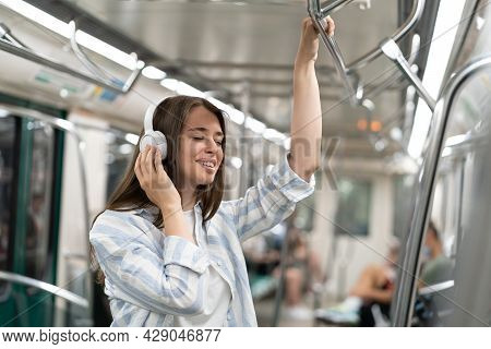 Millennial Woman Listening To Music With Wireless Headphones In Subway Train, Smiling, Dreaming, Hol