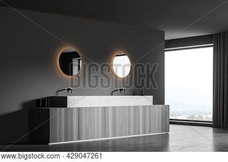 Accent Round Mirrors On The Wall Of Panoramic Dark Grey Bathroom Interior With Floating Sink. Modern