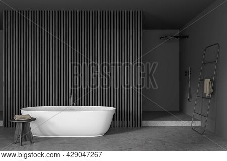 Dark Bathroom Interior With Bathtub, Towel, Closet, Shower, Partition And Oak Wooden Parquet Floor.