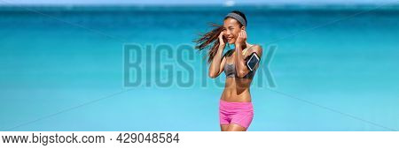 Listening to podcast on phone app with wireless earbuds during beach workout. Fit Asian runner woman happy using wearable technology armband outside banner panoramic.