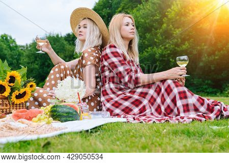 Friends Is Making Picnic Outdoor. Laughing Girls Sitting On White Knit Picnic Blanket Drinking Wine.