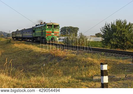 Locomotive With Carriages, Passing On The Railroad Track In The Countryside. Summer Day. Concept Tra