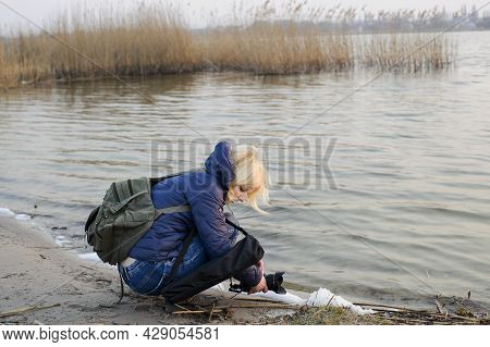 Young Girl Photographer. Photographer By The River, Pictures Outdoor, With Camera And A Backpack. Bl