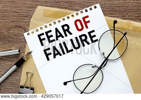 Fear Of Failure. Craft Notebook On Wood Table With Text On Paper And Pen