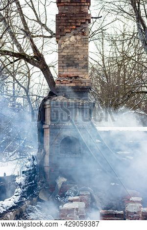 Remains Of A House After A Fire. The Brick Tube Of The Stove Is Shrouded In Dense Smoke. A Vertical