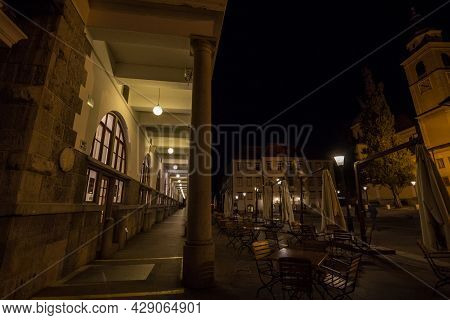 Ljubljana, Slovenia - June 14, 2021: Empty Cafe Terrace And Patios At Nigh In Front Of Columns Of Lj