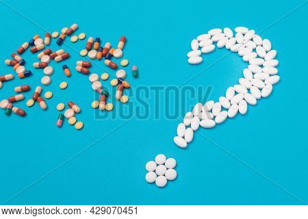 Question Mark Made From White Pills And Tablets With Colored Capsules, Lying On Blue Background. Glo