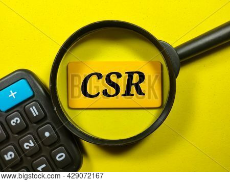 Business Concept.text Csr Writing On Colored Wooden Board With Calculator And Magnifying Glass On A