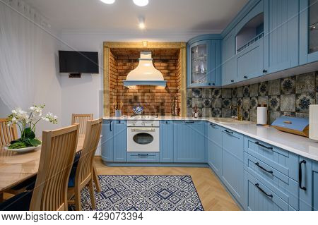 Modern classic blue and beige luxurious kitchen interior with dining table