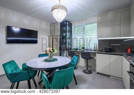Modern large white and grey colored kitchen with dining table, worktop c