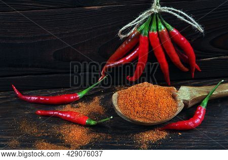 Red Hot Chili Peppers On Wooden Background. Chopped Red Peppers In A Wooden Spoon And Pods Of Red Ch