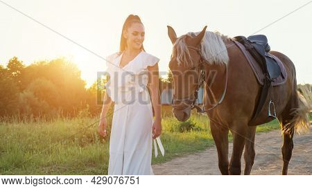 Lady Brunette With Long Hair In Ponytail Wanders With Horse With Saddle Along Ground Road Against Gr