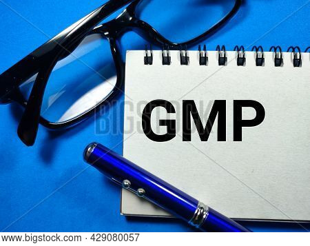 Business Concept.text Gmp Writing On Notebook With Glasses And Pen On A Blue Background.