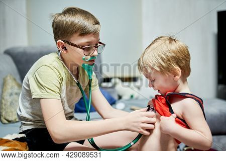 Two Boys 11 Years Old And 3 Years Old Playing Doctor And Patient At Home. Home Life During Quarantin