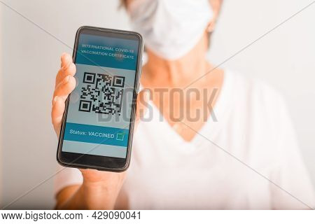 Elderly Woman In Protective Medical Mask Showing Electronic Passport Of A Vaccinated Person Against