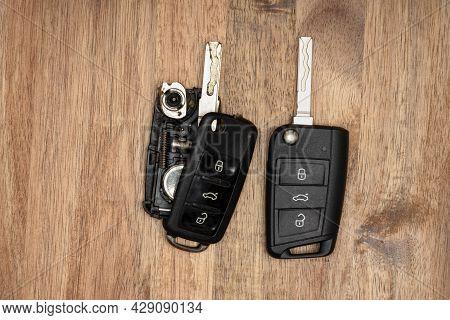 Broken Or Damaged Car Key Fob On Wooden Background. Repair Of Broken Or Damaged Remote Key Fob Locks