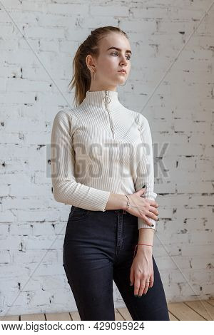 Portrait Of Cute Thoughtful Teen Model Wearing White Sweater And Black Jeans. Caucasian Skinny Young