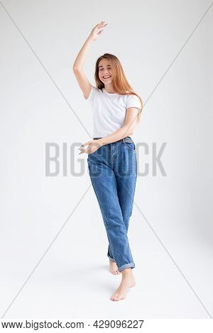 Young Attractive Caucasian Woman With Long Hair In T-shirt And Blue Jeans Dances On White Studio Bac