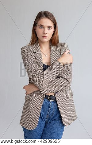 Portrait Of Young Attractive Caucasian Woman With Long Brown Hair In Suit Jacket And Blue Jeans. Ski