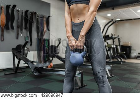 Young Muscular Woman In Sportswear Trains With A Kettlebell In The Gym. Healthy Lifestyle Concept. F