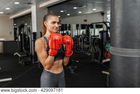 Fit Woman Boxer Trains Hand Punch With Punching Bag In The Gym