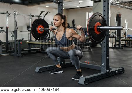 Young Athletic Woman Practicing Squats With A Heavy Barbell On Her Shoulders In The Gym