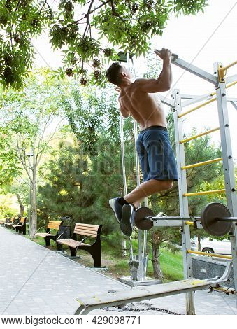 Handsome Man Athlete Workout Outdoors. The Guy Pulls Himself Up On The Horizontal Bar. Healthy Lifes