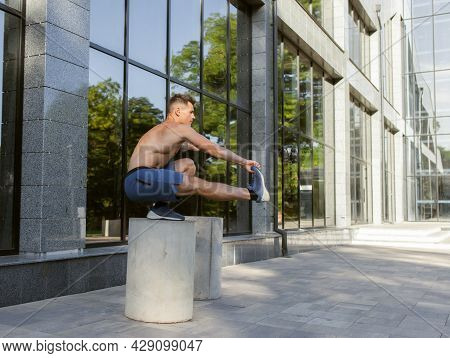 Young Strong Man Is Practicing Squatting On One Leg Outdoors. Healthy Lifestyle Concept