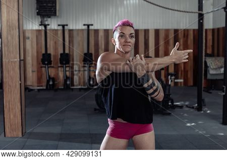 Extraordinary Muscular Powerful Woman With Pink Hair Is Practicing Warm-up Before Intense Workout In