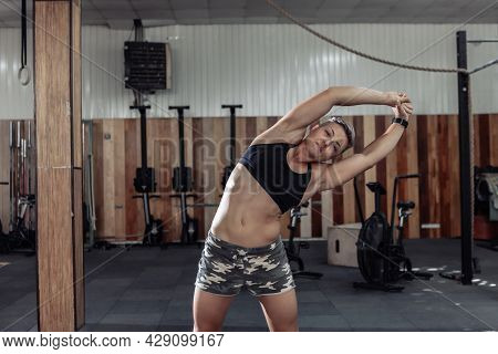 Muscular Powerful Woman Practicing Warm-up Before Intense Workout In A Modern Cross-gym.