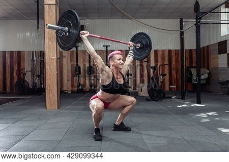 Powerful And Strong Woman Bodybuilder Doing Overhead With Heavy Barbell In Modern Cross Gym. Functio