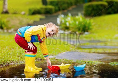 Child Playing With Paper Boat In Puddle. Kids Play Outdoor By Autumn Rain. Fall Rainy Weather Outdoo