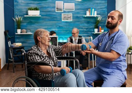 Male Nurse Helping Senior Retired Disabled Woman In Wheelchair To Rehabilitate Using Dumbbels During