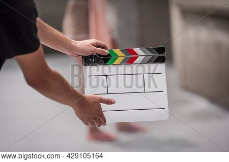 Man Holding A Clapperboard In Front Of The Camera