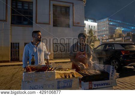 Beyoglu, Istanbul, Turkey - 07.07.2021: Two Vendors Frying Fish On A Portable Mangal Barbecue On Kar