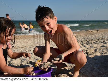 Children Playing At The Sandy Beach. Adorable Kids Building Sandy Castles. Focus On Handsome Funny B