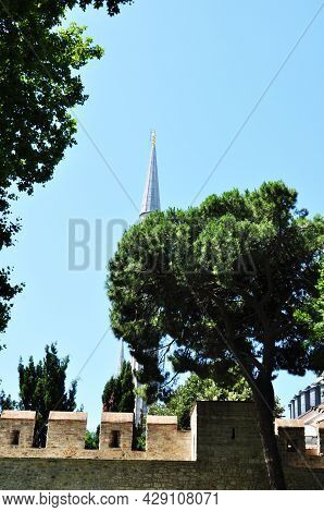 View Of The Minaret Behind The Fence Against The Backdrop Of A Large Green Tree. Clear Sky. Summer.