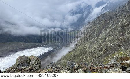 Foggy Mountain Landscape Of North Ossetia. Mountains, Rocks, Hills And A Glacier. Climbing Kazbek Fr