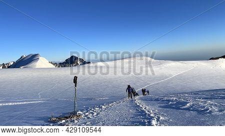 A Group Of Climbers Climb The Mountain Along A Snowy Path. Mountain Landscape Of North Ossetia. Clim