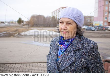 An Elderly Woman On The Street Looks Into The Distance. An Elderly Woman In A Hat And Coat. Portrait